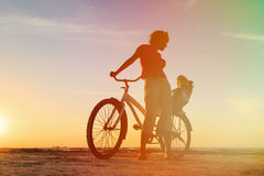 Mother and baby biking at sunset Stock Images