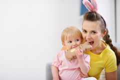 Mother and baby biting Easter rabbit cookie Royalty Free Stock Photos