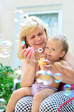 Mother with baby blowing soap bubbles Royalty Free Stock Images