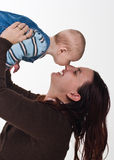 Mother and baby boy. A happy mother and her baby boy touching each other's noses. She is holding him high Stock Photos