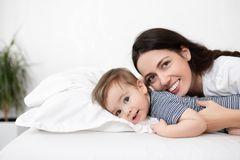 Mother and baby boy on bed stock image
