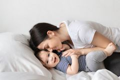 Mother and baby boy on bed stock photo