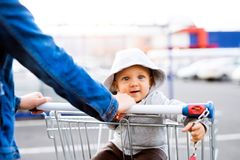 Mother with baby boy in the car park, going shopping. Unrecognizable mother with baby boy in the car park, going shopping. Toddler boy sitting in a shopping Royalty Free Stock Photography