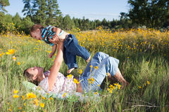 Mother and baby boy cuddling. Outdoors in flowers Stock Photo