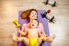 Mother with baby boy exercising on the floor. Young mother with her baby son lying on the fitness mat during the exercise with dumbbells on the floor stock image