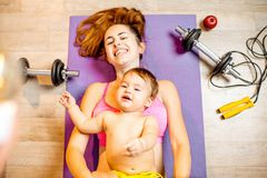 Mother with baby boy exercising on the floor. Young mother with her baby son lying on the fitness mat during the exercise with dumbbells on the floor royalty free stock image