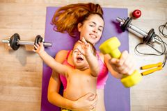 Mother with baby boy exercising on the floor. Young mother with her baby son lying on the fitness mat during the exercise with dumbbells on the floor royalty free stock photos