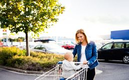 Mother with baby boy going shopping in the car park. Royalty Free Stock Images