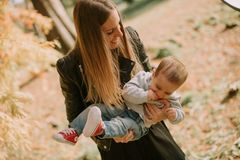 Mother and baby boy having fun in autumn park stock photo