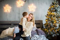 Mother and baby boy on New Year background. Happy family portrait of mother and baby boy sitting on cosy bed in festivaly decorated room with Christmass tree royalty free stock photos