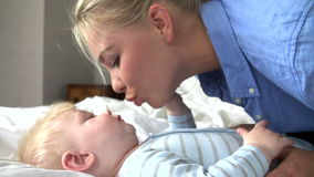 Mother And Baby Boy Playing In Bed stock video footage