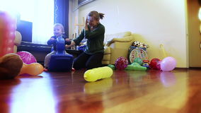 Mother and baby boy playing, ridding a toy horse. Mother and baby boy playing ridding a toy horse, video footage stock video footage