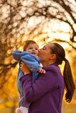 Mother and baby boy. Portrait of mother and baby boy in the park in the autumn. Mother giving a kiss Royalty Free Stock Photography