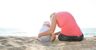 Mother and baby boy sitting on the sandy beach Stock Images