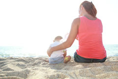 Mother and baby boy sitting on the sandy beach Royalty Free Stock Photography