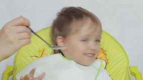 Mother baby boy trying to feed with a spoon, but he refuses and laughs. Close-up stock video