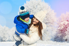 Mother and baby boy in the white snowy day, winter vacation Royalty Free Stock Images