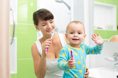 Mother with baby brushing teeth in bathroom Royalty Free Stock Photos