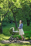Mother with baby carriage Stock Images