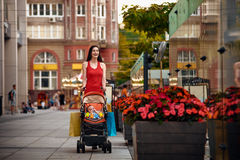 Mother with baby carriage on city street summer Royalty Free Stock Photography