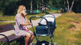 Mother with baby carriage and speaking on phone in summer park. Sunny. Walking stock video