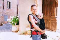 Mother with baby in carrier in the old town of Pula, Croatia. Beautiful young mother with baby child in carrier in the old town of Pula, Croatia. Travel family Royalty Free Stock Photos