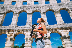 Mother with baby in carrier in the old town of Pula, Croatia. Beautiful young mother with baby child in carrier in the old town of Pula, Croatia. Travel tourist Royalty Free Stock Images