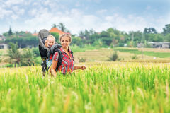 Mother with baby in carrying backpack walking on rice terraces. Cheerful mother with baby boy in carrying backpack walking on green rice terraces. Traveling with Stock Photography