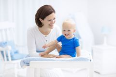 Mother and baby on changing table. Mother and baby in diaper on changing table. Mom changing nappy on baby boy. Kids nursery. Infant hygiene and care products Stock Images