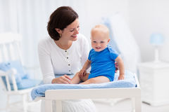 Mother and baby on changing table Royalty Free Stock Images