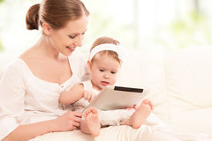 Mother and baby child with tablet computer on the couch at home Stock Photo