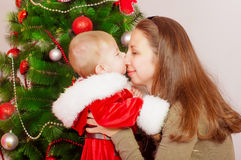 Mother and baby  at Christmas Tree Stock Photo