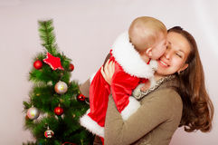 Mother and baby  at Christmas Tree Stock Images