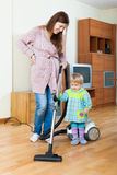 Mother with baby cleaning home stock photo