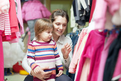 Mother with baby at clothes store. Happy mother with baby chooses wear at clothes store stock image