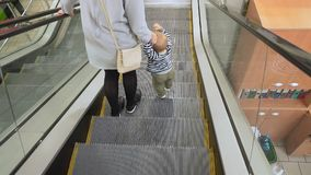 Mother and baby come out of escalator stock video