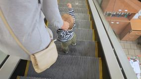 Mother and baby come out of escalator stock video footage