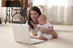 Mother and Baby with a Computer. Horizontal image of a young mother and her baby looking at a laptop computer Royalty Free Stock Image