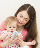 Mother with the baby is considering a toy. Royalty Free Stock Images