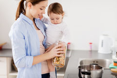 Mother and baby cooking pasta at home kitchen. Family, food, healthy eating and people concept - happy mother and little baby girl cooking pasta for dinner Royalty Free Stock Photography
