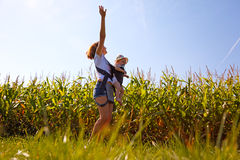 Mother with baby on the corn field. Beautiful women turns little baby in backpack on the corn field Stock Photography