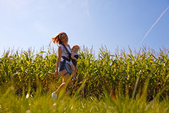 Mother with baby on the corn field. Beautiful women turns little baby in backpack on the corn field Royalty Free Stock Image