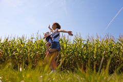Mother with baby on the corn field. Beautiful women turns little baby in backpack on the corn field Royalty Free Stock Photo