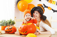 Mother and baby cut  pumpkin for Halloween in kitchen Stock Photos