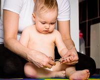 Mother and baby - cutting nails Royalty Free Stock Images