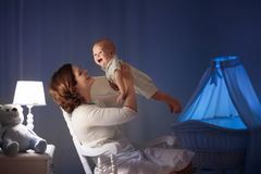 Mother and baby in dark bedroom royalty free stock photos