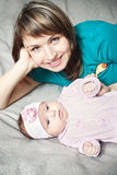 Mother and baby daughter. Young smiling mother with her baby daughter in pink crawlers lying on bed Stock Photo