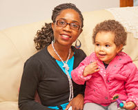 Mother and baby daughter. Smiling Angolan mother with baby daughter wearing winter coat and ready  for the Winter weather Stock Image