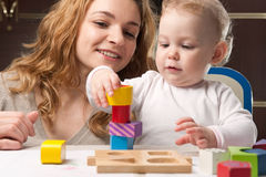 Mother and baby daughter building tower Stock Image