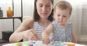 Mother and baby daughter doing craft work at home stock video